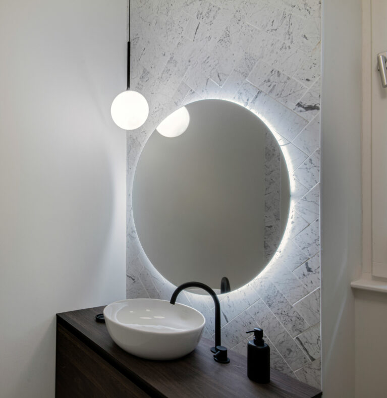 AQSO arquitectos office. The bathroom vanity unit is made of dark teak wood. The lighting comes from the circular backlit mirror and the globe lamp suspended from the ceiling.