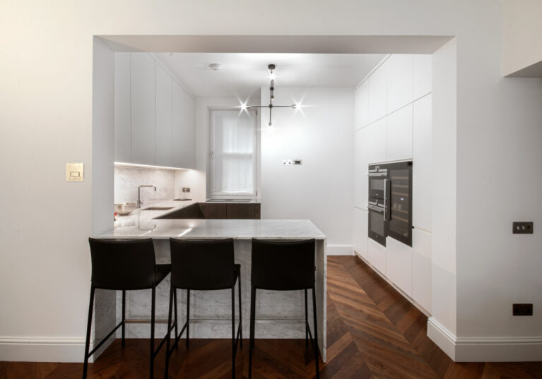 AQSO arquitectos office. From the living room, the kitchen is perceived as an extension of the space. The threshold separating the two rooms is delimited by a peninsula worktop with stools.