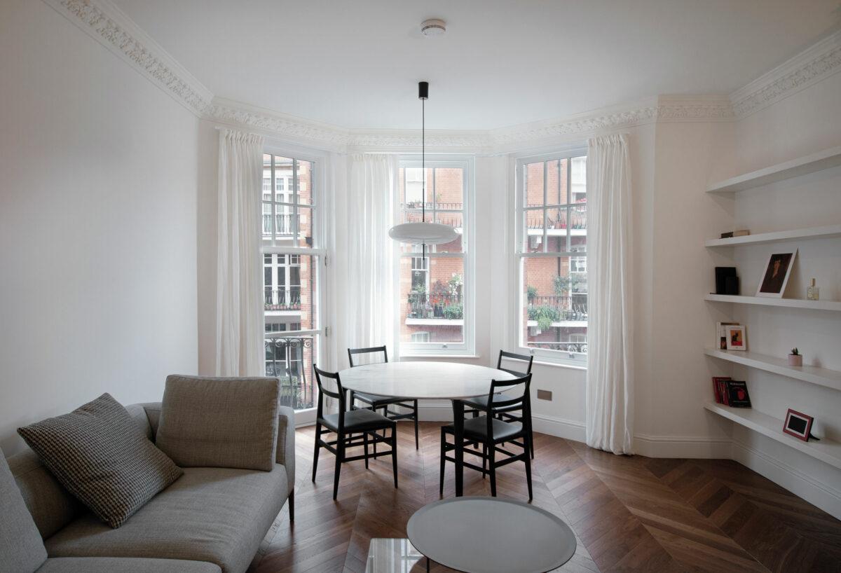 AQSO arquitectos office. El salón comedor disfruta de las vistas a la calle, y tiene acceso al balcón. El suelo de tarima de madera en espiga contrasta con el blanco de las paredes y techos y los colores neutros del mobiliario.