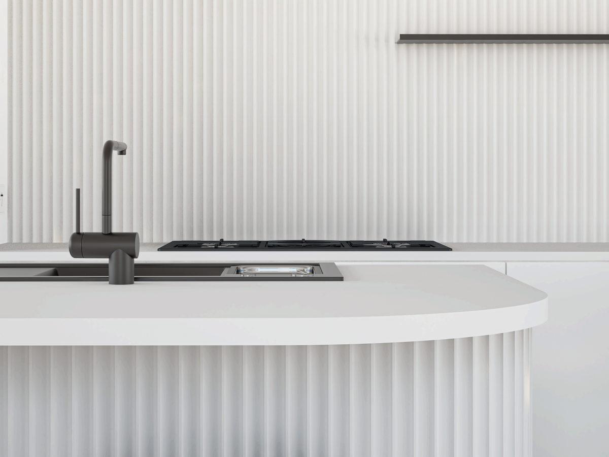 AQSO arquitectos office. Detalle de la isla de la cocina, con paredes de azulejo cerámico vertical y grifería minimalista de color negro mate.